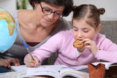 Woman helping her granddaughter with her homework — Stock Photo