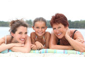 A 30 years old woman, a little girl and a 55 years old woman lying down on — Stockfoto