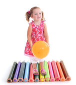 Photomontage of little girl with balloon walking on crayons — Stock Photo