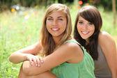 Teenage girls sitting in a field — Stock Photo