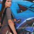 Woman holding a guitar and posing in front of a graffiti wall - Stock Photo