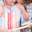 Stock Photo: Affectionate womkissing her husband white preparing meal