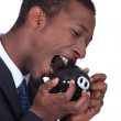 Man trying to bite open a piggy bank — Stock Photo