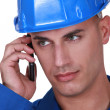 Tradesman talking on his mobile phone - Stock Photo