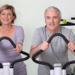 Senior couple riding bikes in the gym — Stock Photo #8953175