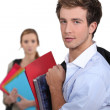 Two students carrying schoolwork — Stock Photo