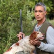 Foto Stock: Hunter taking rifle and caressing hunt dog