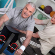 Stock Photo: Older mexercising with personal trainer