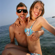 Man carrying his girlfriend at the beach - Stock Photo