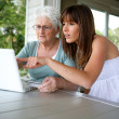 Stock Photo: Grandmother and her granddaughter doing computer