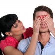 Woman covering boyfriends eyes — Stock Photo