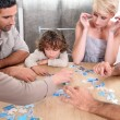 Family completing jig-saw puzzle — Stock Photo