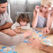 Stock Photo: Family completing jig-saw puzzle