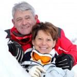 Smiling senior couple laid in snow — Stock Photo #8955716