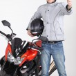 Young man holding driving license stood next to motorcycle — Stock Photo