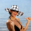 Woman at the beach giving thumb-s up — Stock Photo #8956593