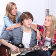Stock Photo: Teenage boy playing electric guitar next to two girls