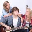 Teenage boy playing electric guitar next to two girls — Stock Photo
