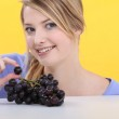 Blonde woman showing grapes — Stock Photo #8956694