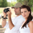 Couple with a camera in the countryside — Stock Photo