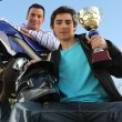 A man with a motorcycle and a trophy. — Stock Photo
