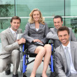 Female executive in wheelchair with colleagues outside office building — Stock Photo