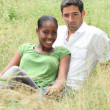 Couple sat in a field - Stock Photo