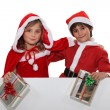 Foto Stock: Two children wearing Christmas costumes