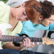 Stock Photo: Young couple tuning and playing guitar