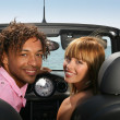 Couple sat in convertible car at the seaside - Stock Photo