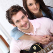Young woman and young man with guitar — Stock Photo #8957799