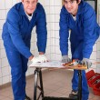 Two skilled tradesmin blue jumpsuites watching drawing — Photo #8958116