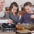 Stock Photo: Womcooking crepes with her daughters