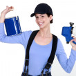 Woman holding paint sprayer - Stock Photo