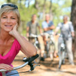 Older female cyclist riding with friends in the forest - Foto Stock