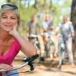 Older female cyclist riding with friends in the forest - Stockfoto