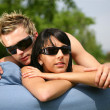 Couple sunbathing on a sofa — Stock Photo