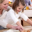 A mother teaching her daughter how to bake. - Stockfoto