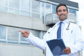 Doctor pointing outside — Stockfoto