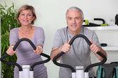 Senior couple riding bikes in the gym — Stock Photo