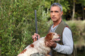Hunter taking a rifle and caressing a hunt dog — Stockfoto
