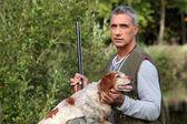 Cazador de tomar un rifle y acariciando un perro de caza — Foto de Stock