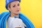 Female plumber with blue pipe — Stock Photo