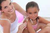 A woman putting suncream on her daughter. — Foto de Stock