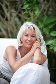 Senior woman sitting on an outdoor sofa — Stock Photo