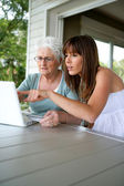 A grandmother and her granddaughter doing computer — Stock Photo