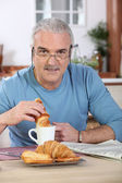 Senior man having breakfast — Stock Photo