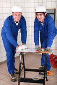 Two skilled tradesman in blue jumpsuites watching a drawing — Zdjęcie stockowe