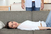 Woman laying on couch husband stood behind — Stok fotoğraf