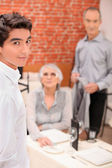 Young waiter serving an older couple in a restaurant — Stock Photo